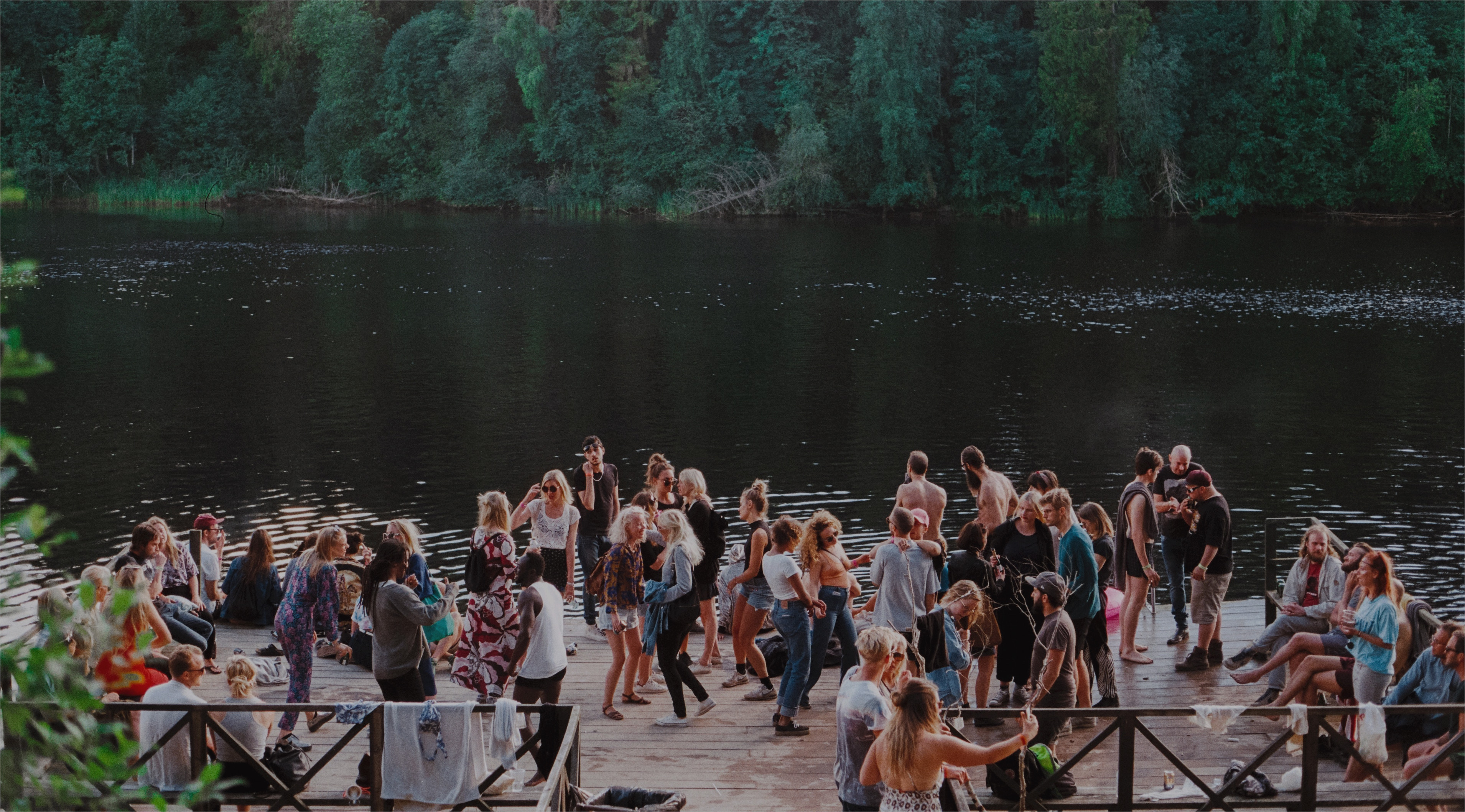 A group partying on a dock at the lake.